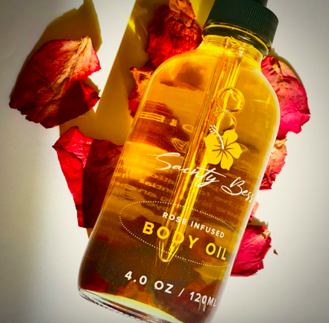 A bottle of the body oil arranged on rose petals