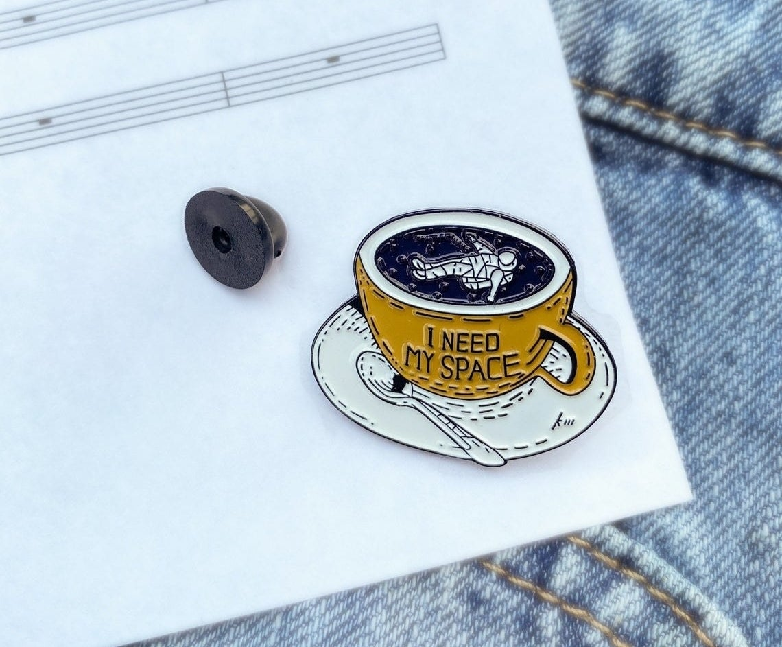 A pin with an astronaut floating in a coffee cup that says I need space