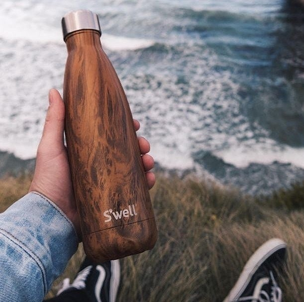 A hand holding a S'well water bottle with a wood-mimic finish