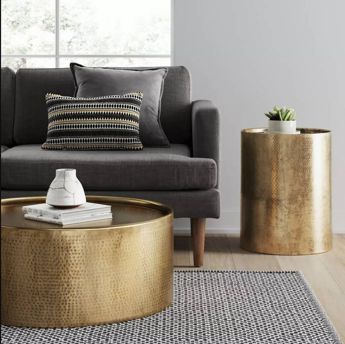 A gold side table next to a couch in a living space