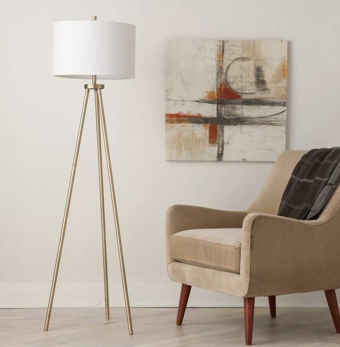 The lamp with gold chrome legs next to a chair