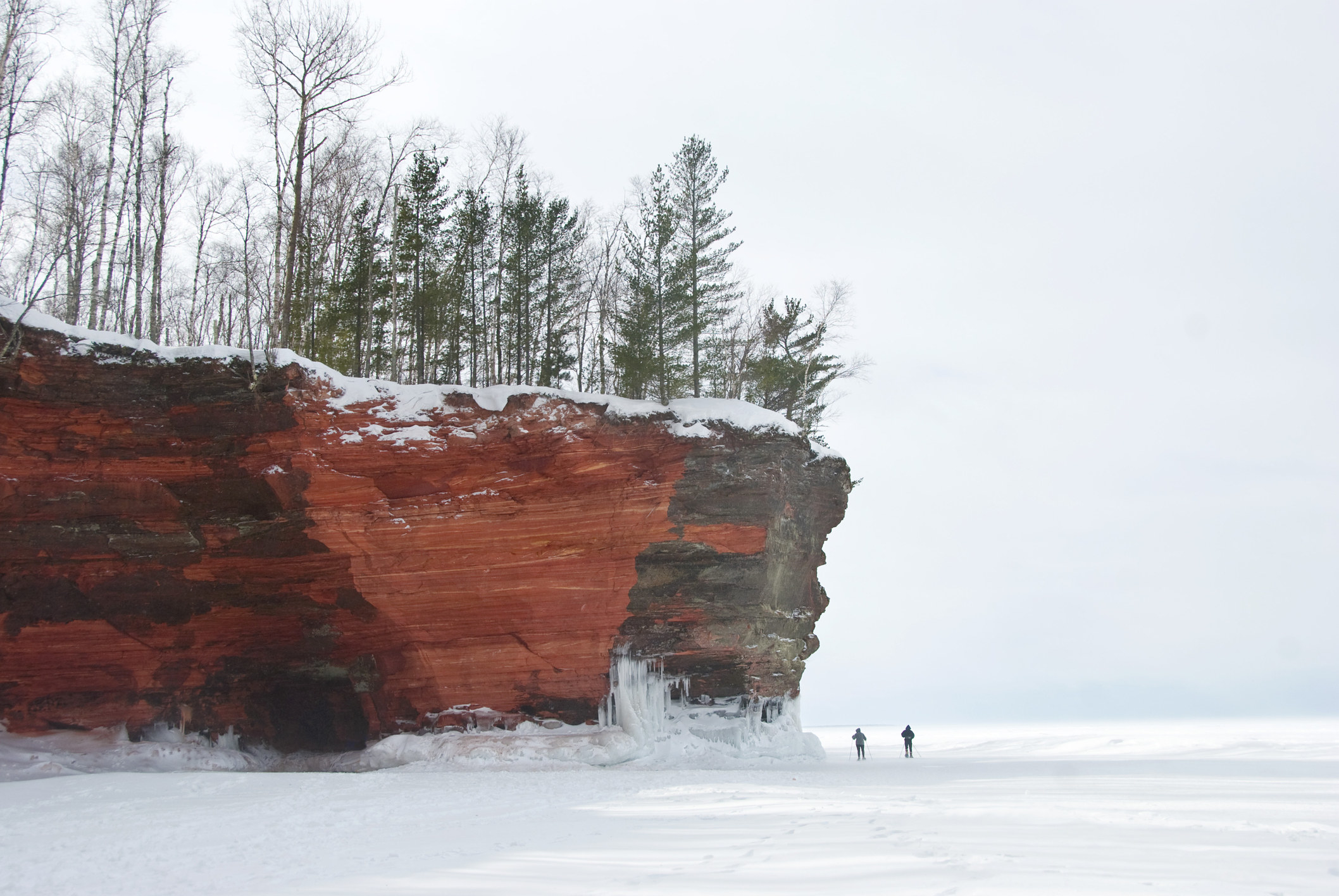 Red, sandstone cliffs jut out over a frozen lake where two small figures walk