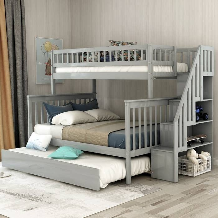 Light gray bunk bed with trundle, and blue, brown and white bedding