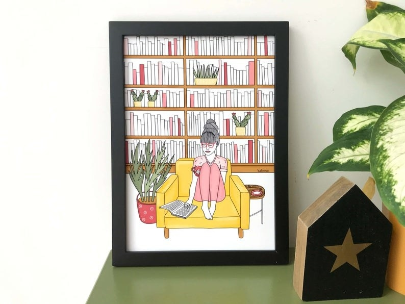 An art print of a person sitting on a couch in their library reading a book