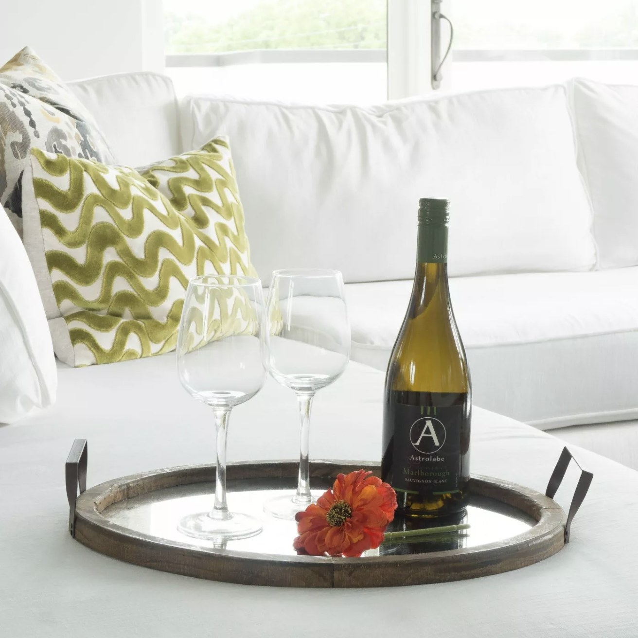 The wood tray with distressed mirror on a couch with wine and two wine glasses on top