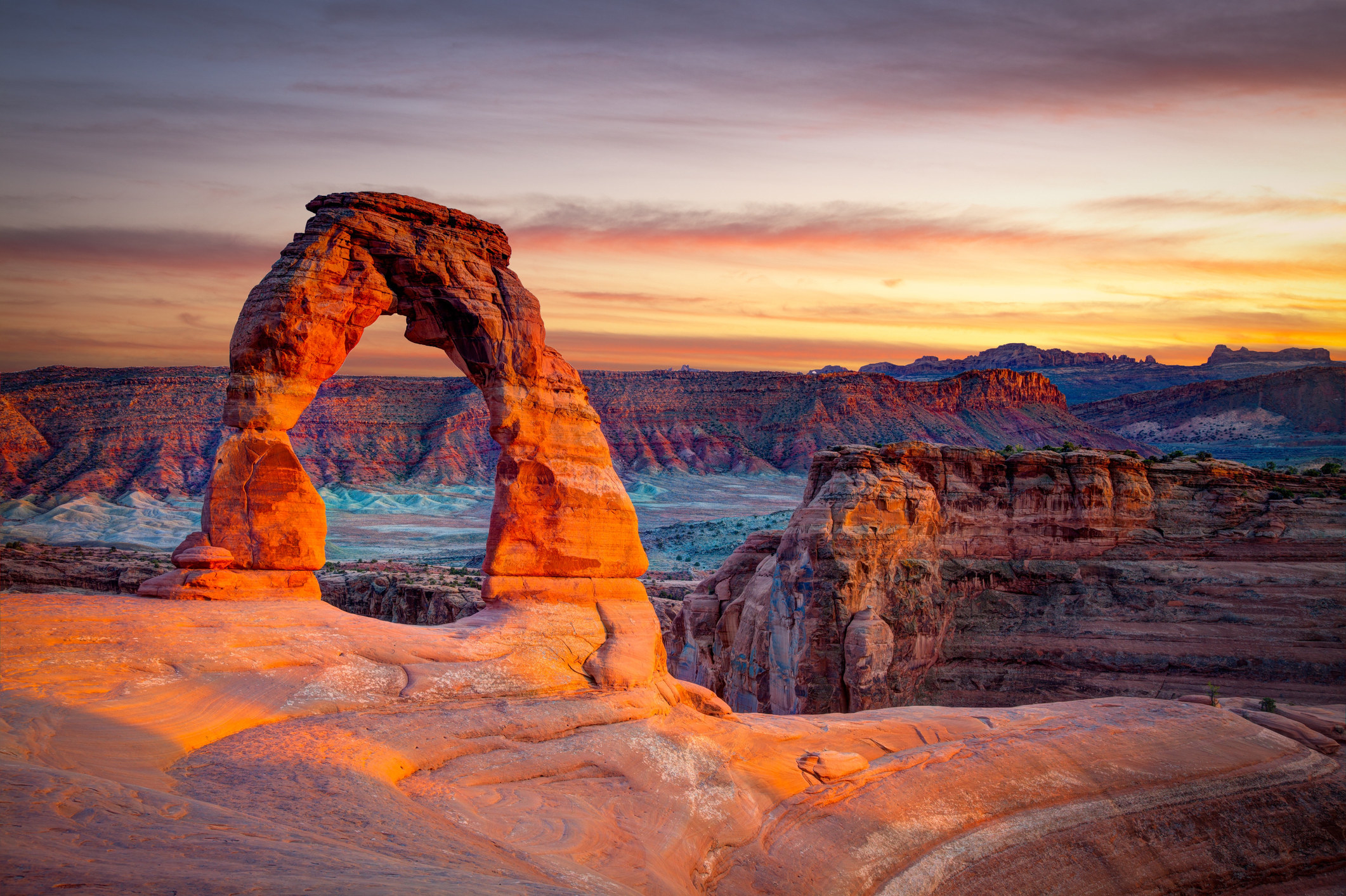 An arch at Arches National Park sits in the foreground with cliffs and a sunset behind it