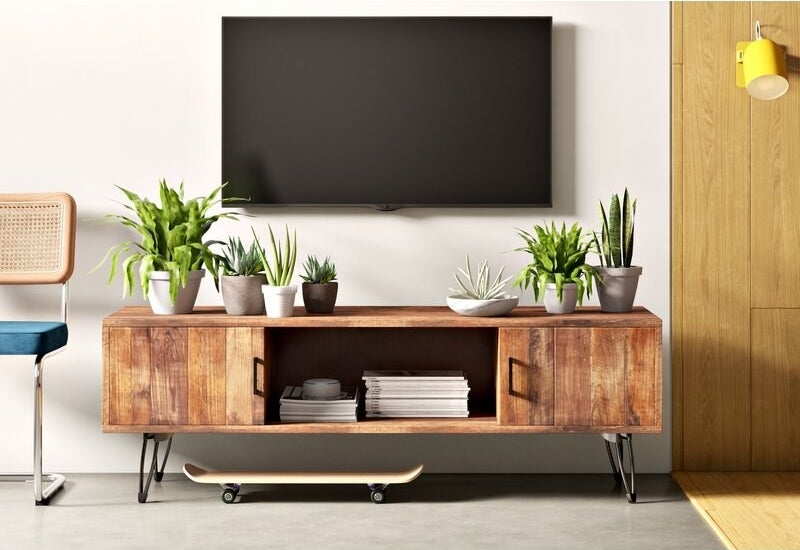 A reclaimed wood TV stand with hairpin legs and storage cabinets