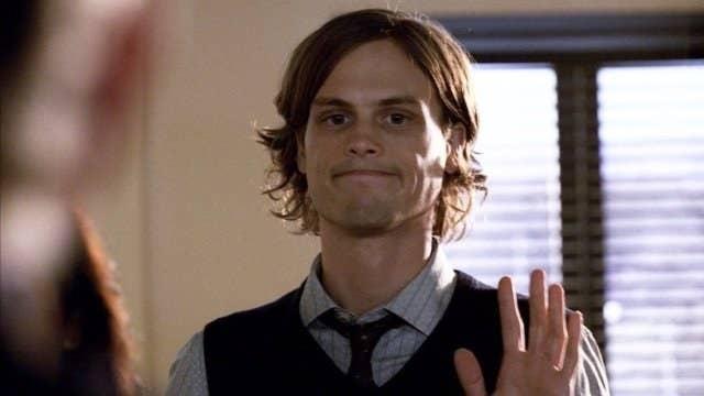 Spencer waving and smiling awkwardly.