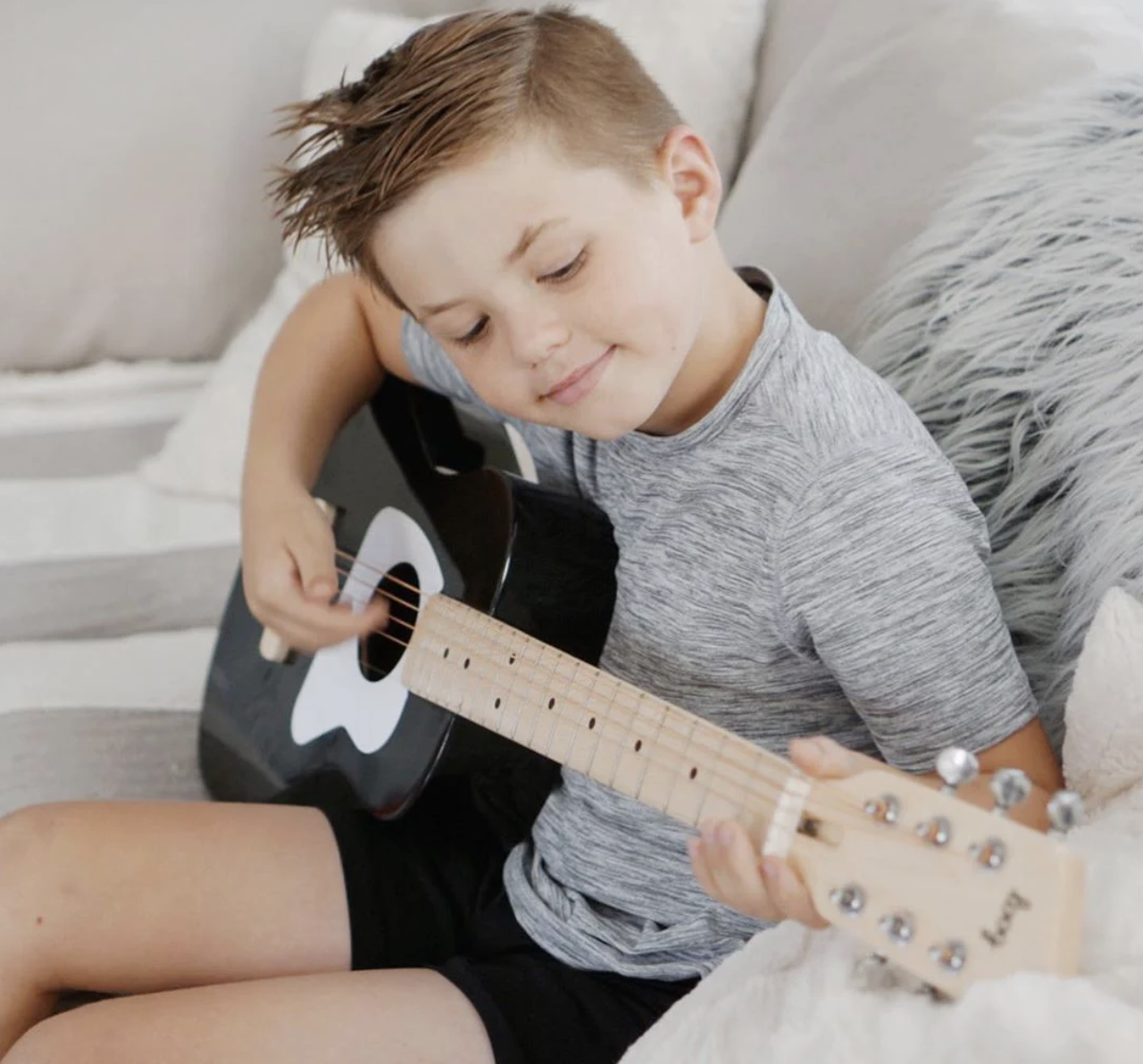 A kid playing the black guitar