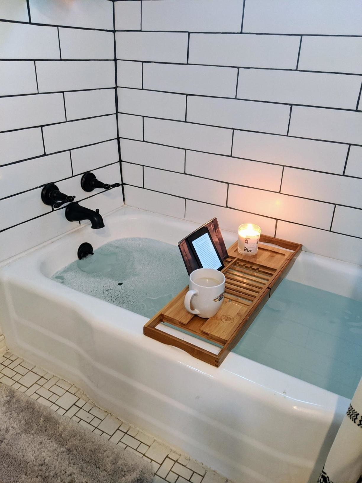 The caddy with a coffee mug, candle, and Kindle on it over a bathtub