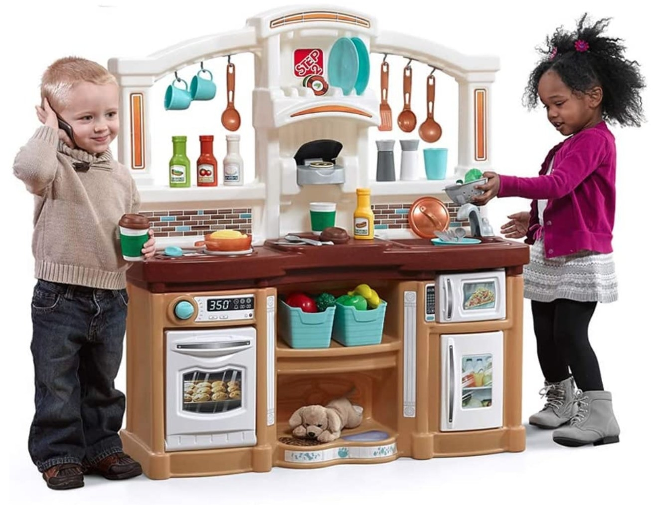 Two young children pretend to cook at a toy kitchen.