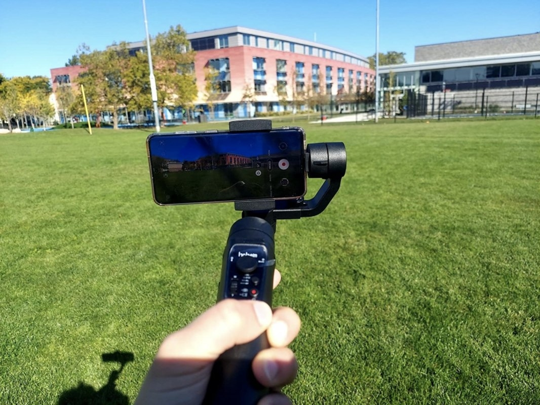 An iPhone is held using the stabilizer in front of a park