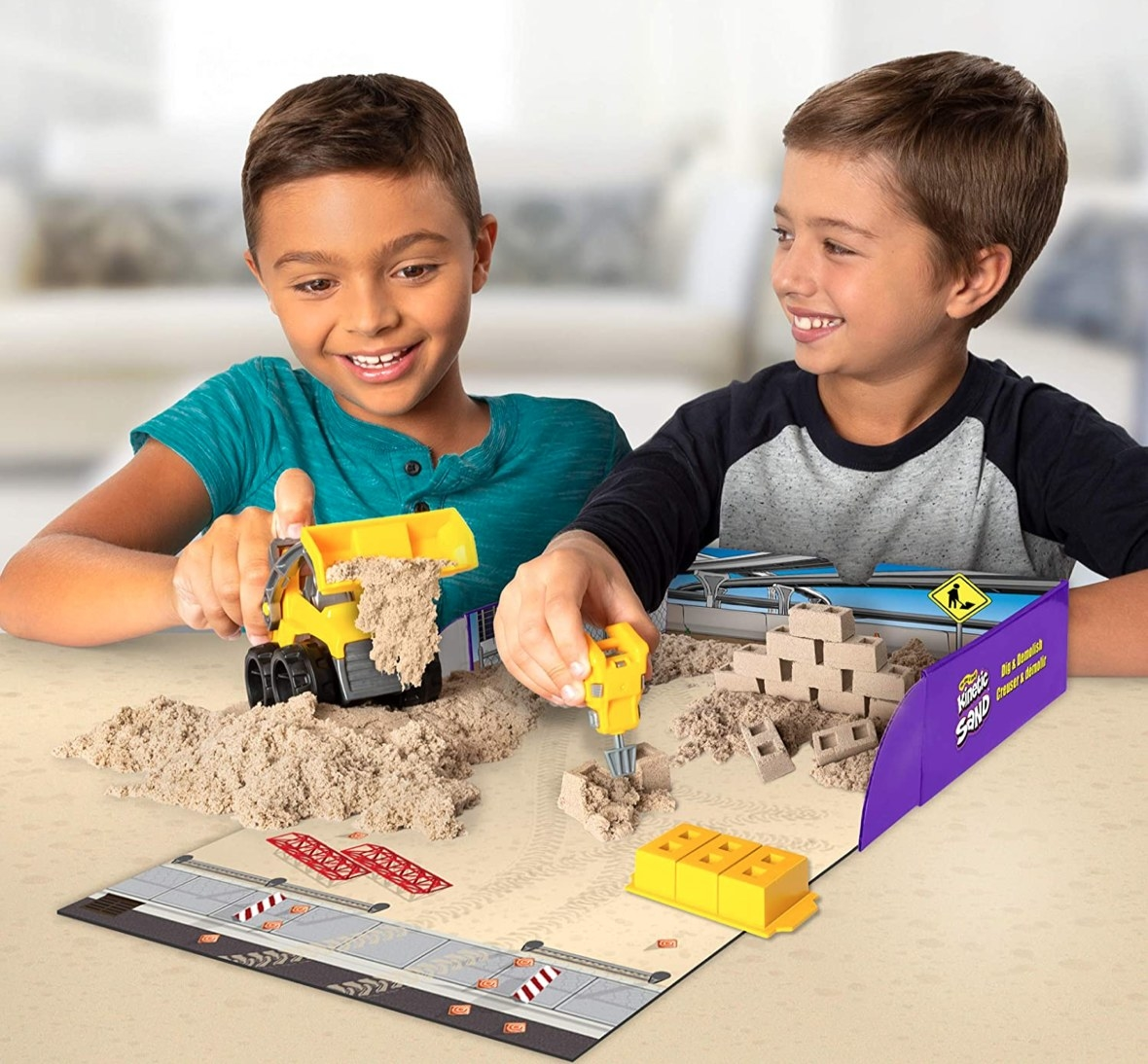Two boys play with a a truck in a kinetic sand set.