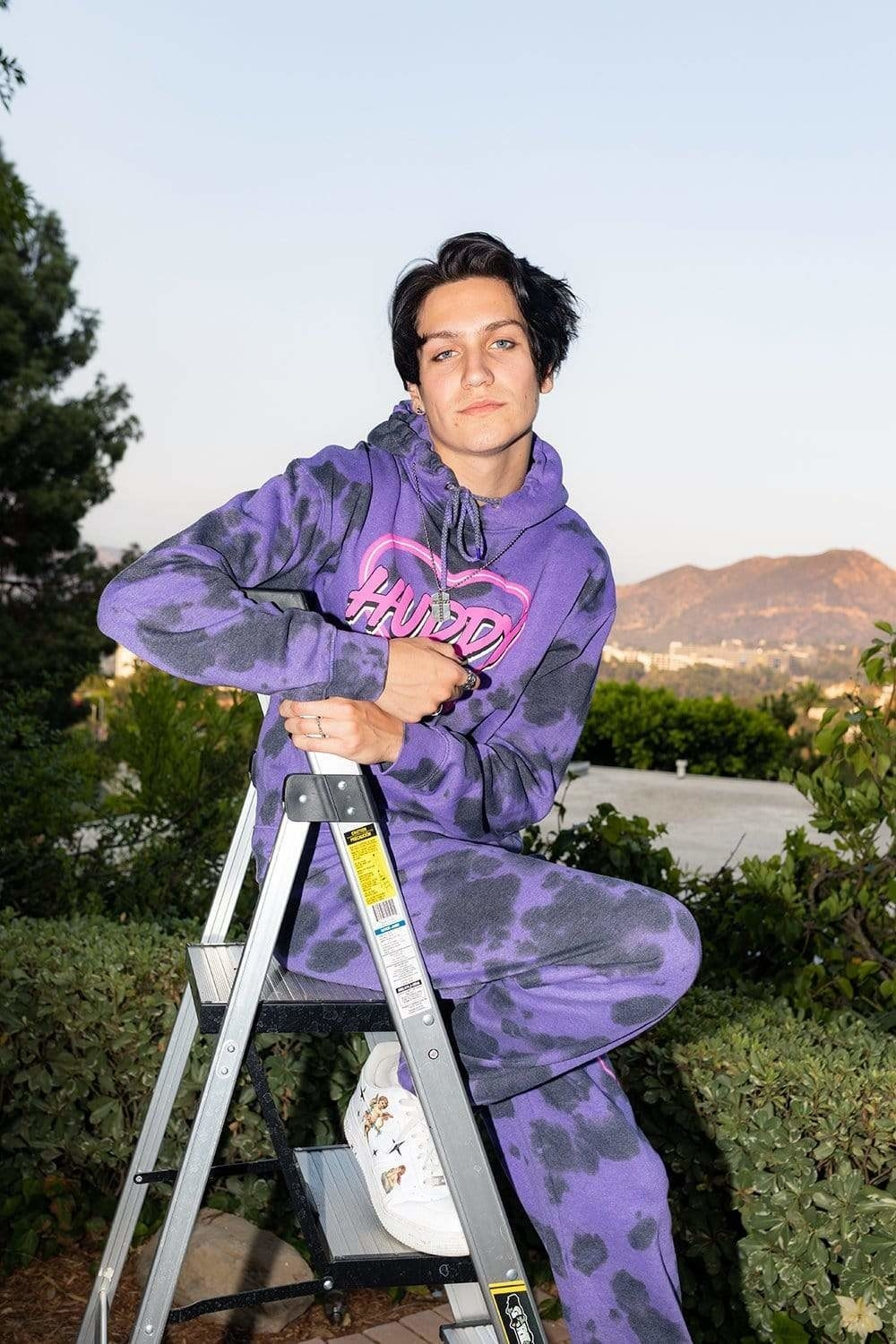 Chase poses in a purple tie dye hoodie