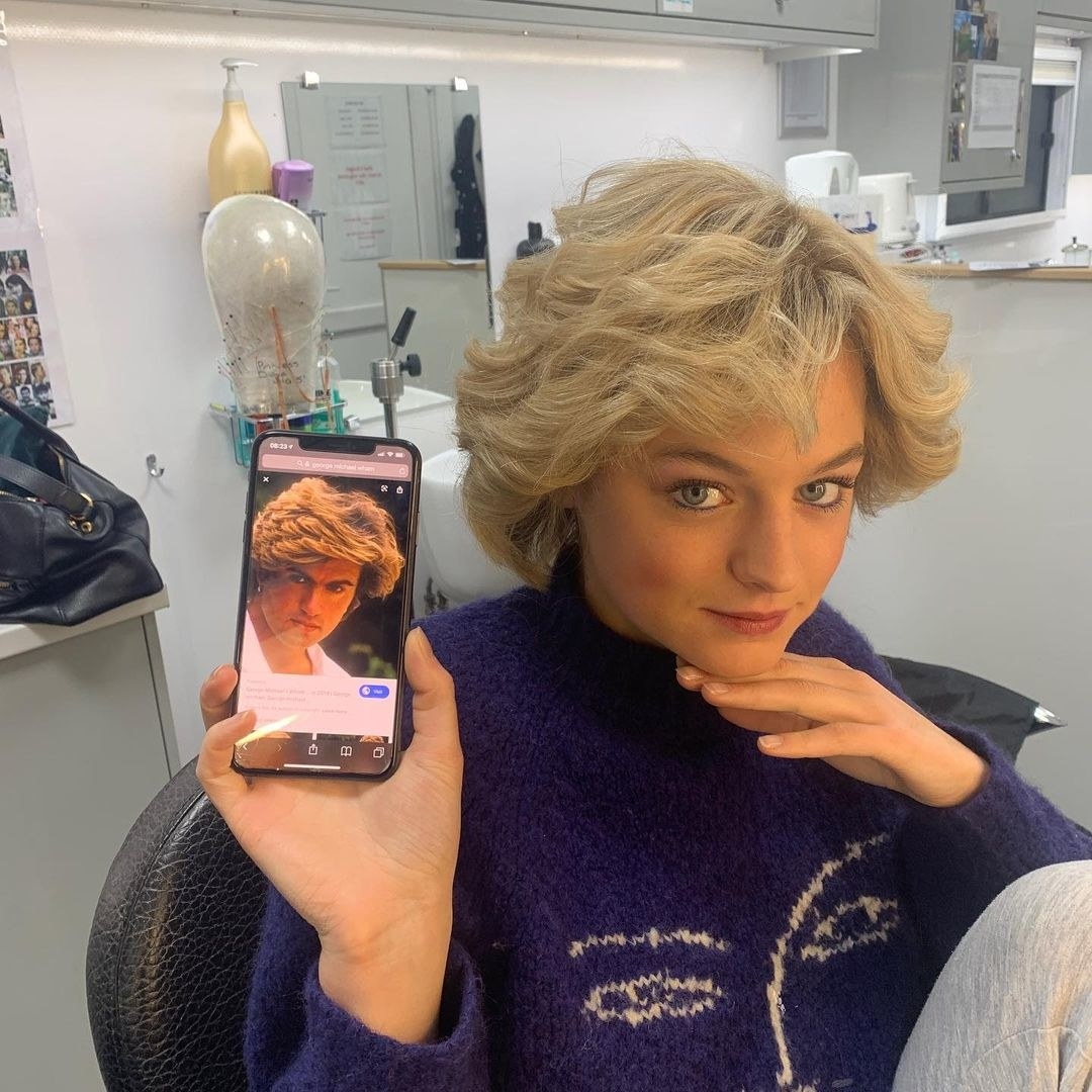 Emma Corrin sitting in a dressing room trailer; she has her hand tucked under her chin as she points her phone at the camera; her phone has an image of a blonde-haired man with a shaggy hairstyle