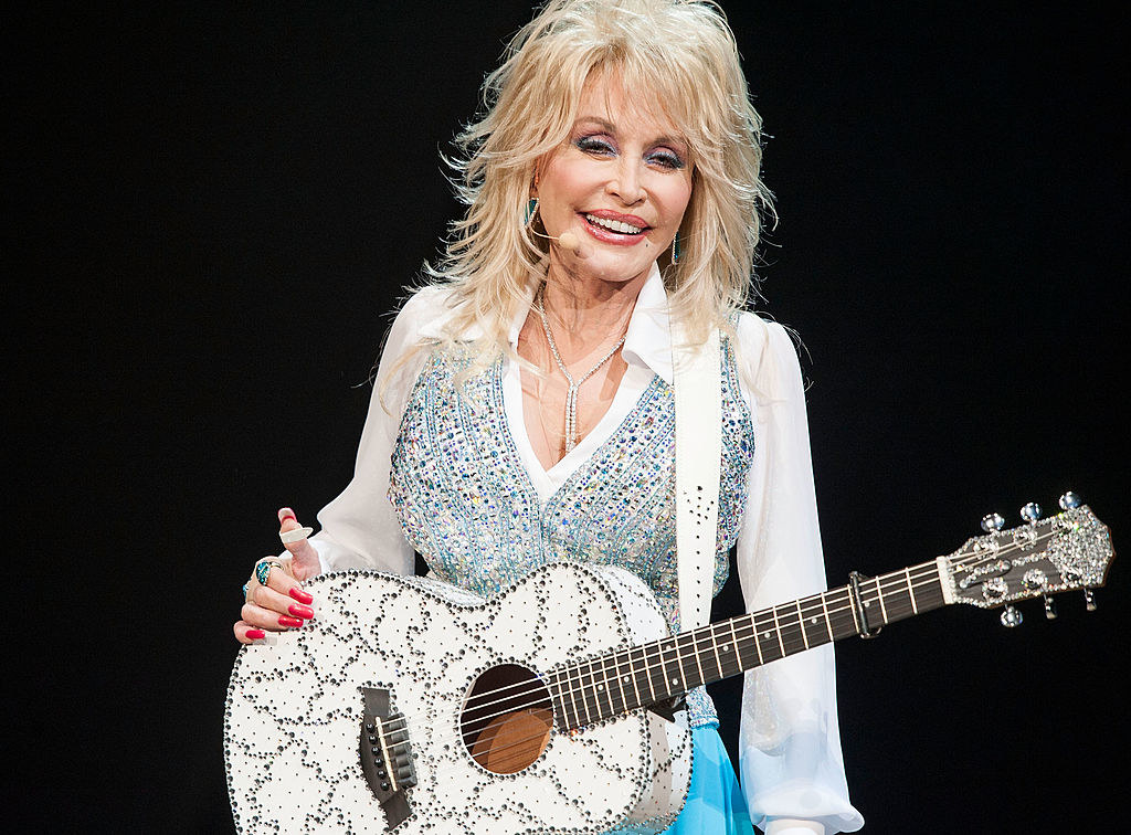 Dolly smiling on stage with a guitar