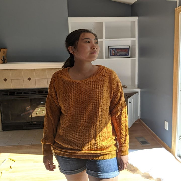 reviewer wearing the sweater in a ginger gold
