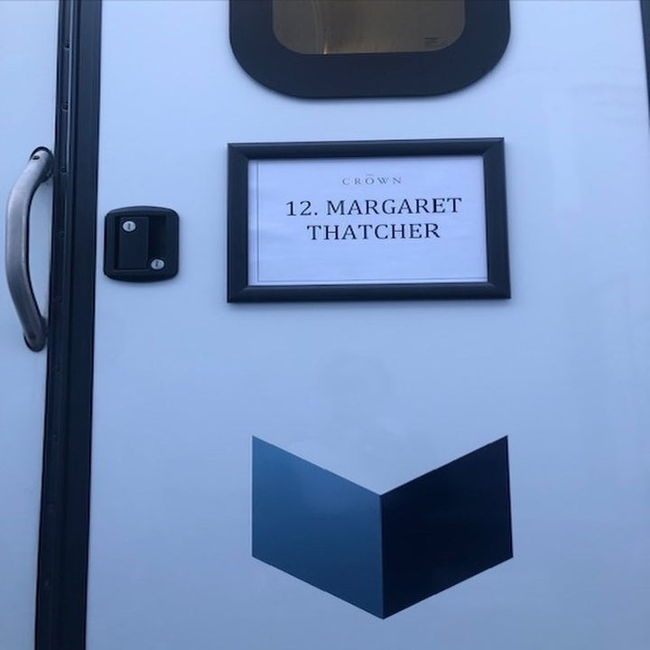 "A door to a dressing trailer; there is a sign that reads ""The Crown"" in small print, while ""12 Margaret Thatcher"" is written in a bold print"