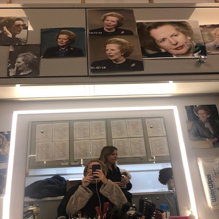 Gillian Anderson taking a photo in her dressing room trailer; there are pictures of Margret Thatcher on the walls as inspiration