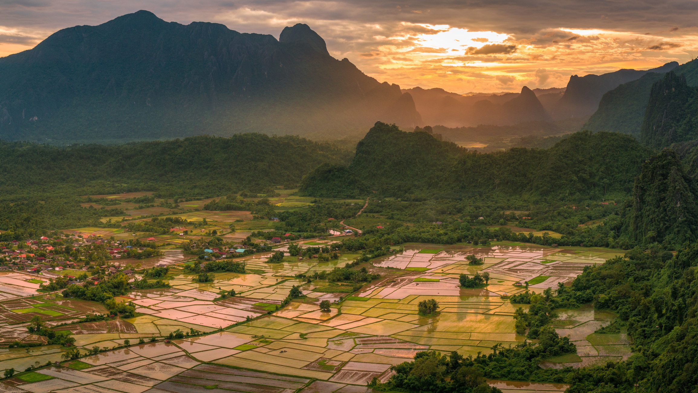 A view over rice paddy fields with big rocky mountains behind them at sunset