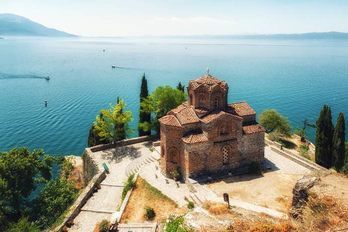 An old brick monastery set on a cliff overlooking a giant blue lake dotted with boats