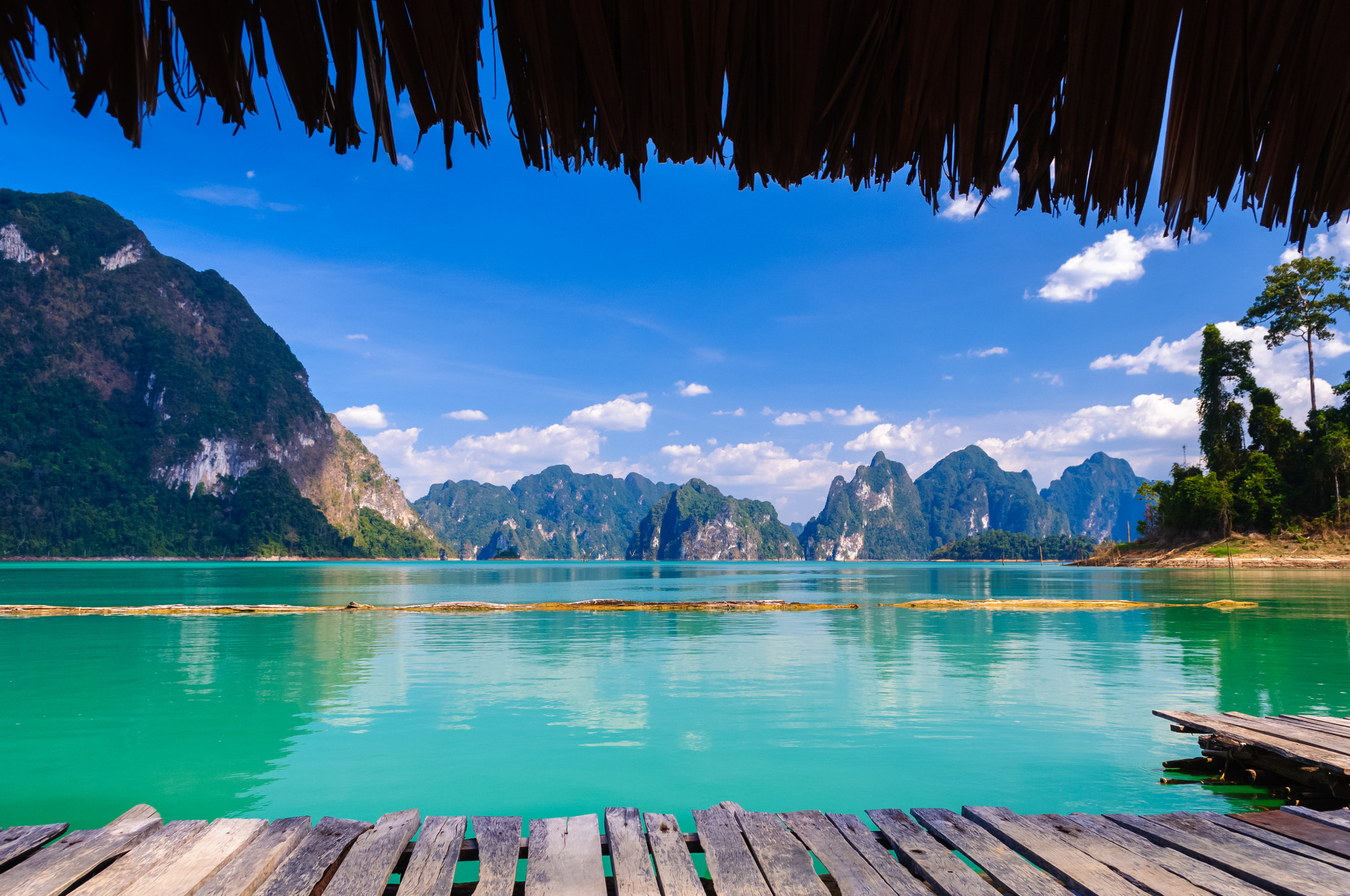 A photo taken from the wooden deck of a floating hut, looking out on a turquoise lake dotted with jagged mountains