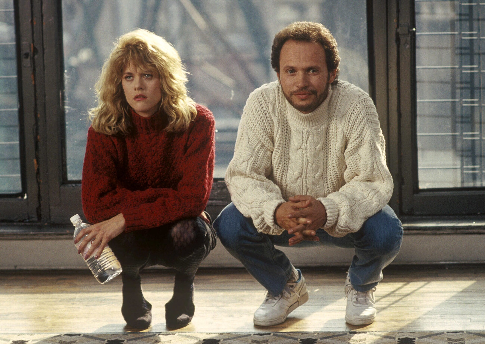 Still from When Harry Met Sally: Meg Ryan and Billy Crystal squat side by side, smiling at each other