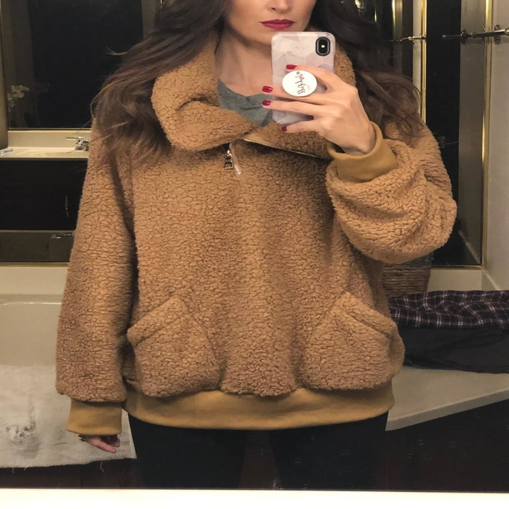 reviewer wearing sweater in brown