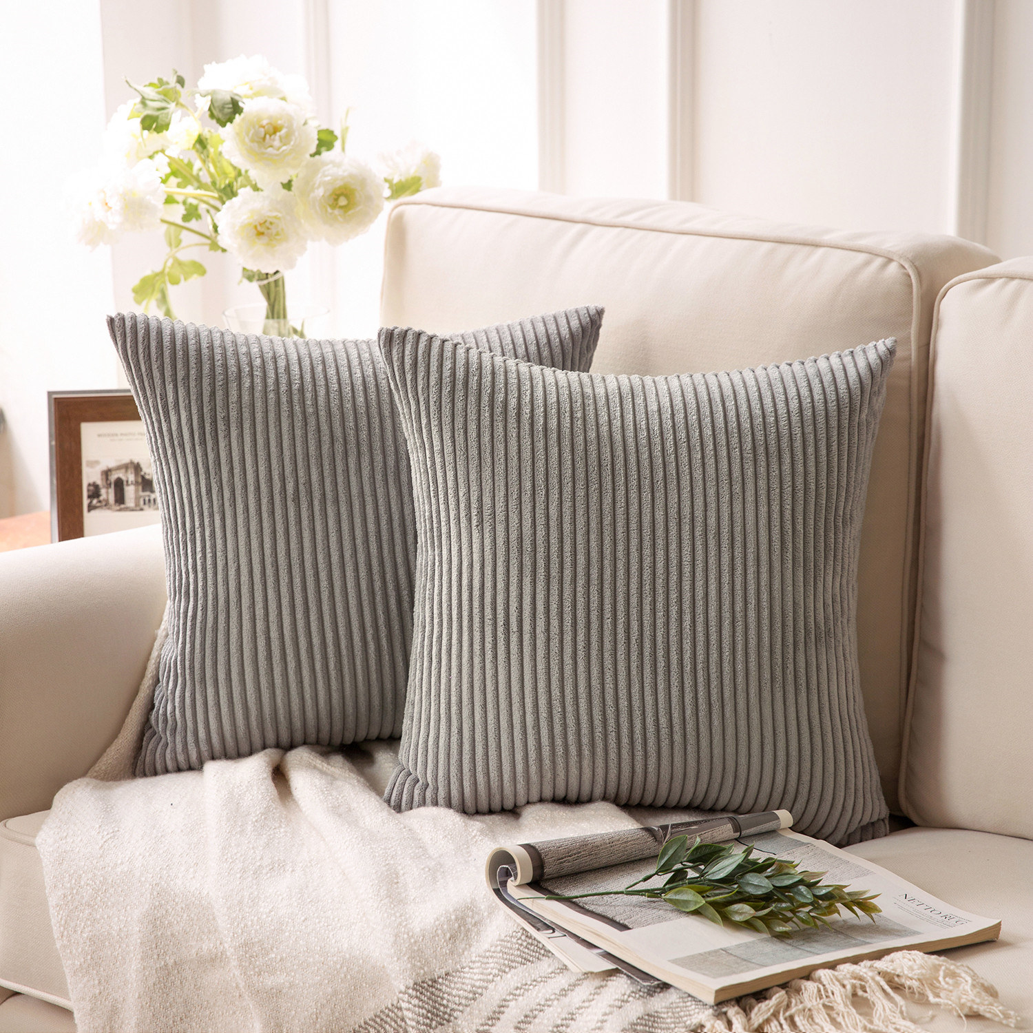 the pillows in grey displayed on a couch on top of a throw