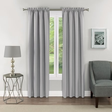 the curtains in gray hung on a rod next to a lamp on a table and a couch