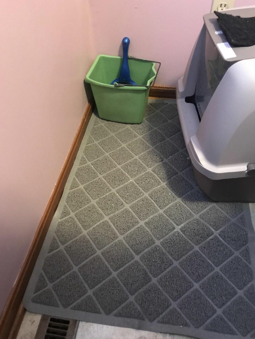 a grey litter mat under a hooded litter box