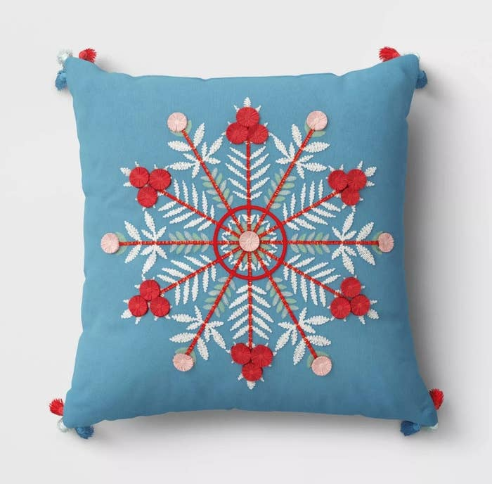 Blue pilow with red white and pink embroidered snowflake/blue, white and red pompoms on corner