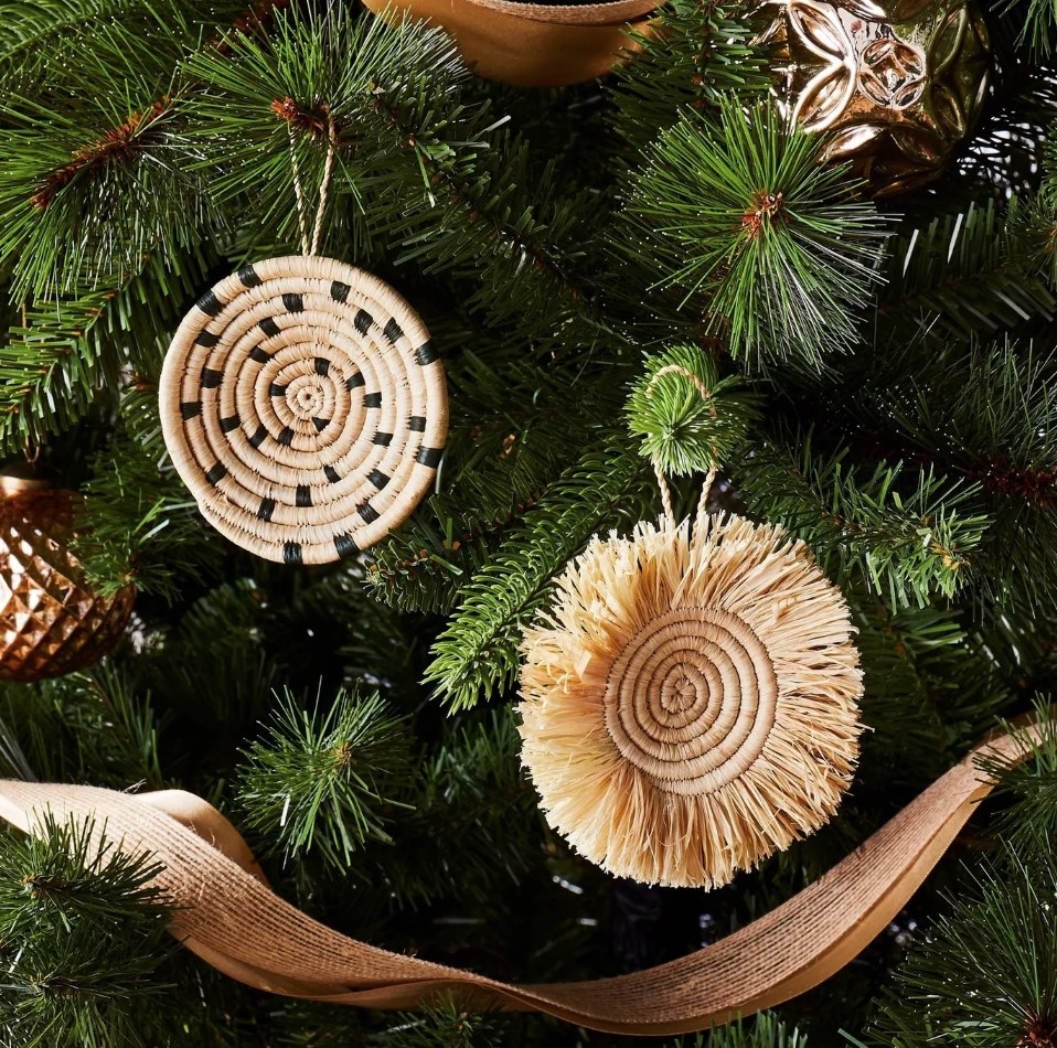 Woven christmas ornaments, left one woven spiraled disc with black accents, right beige spiraled disc with fringe