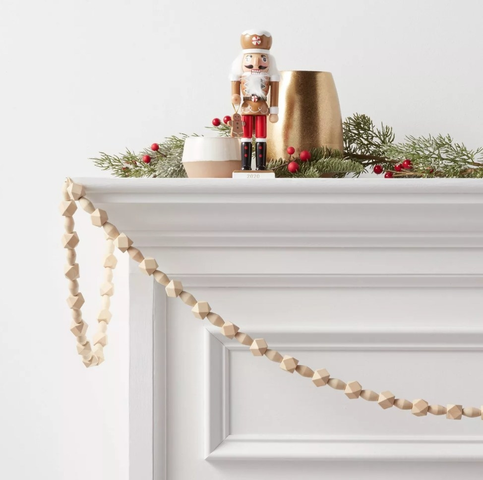 Sandy beige colored beaded garland hanging over white mantel