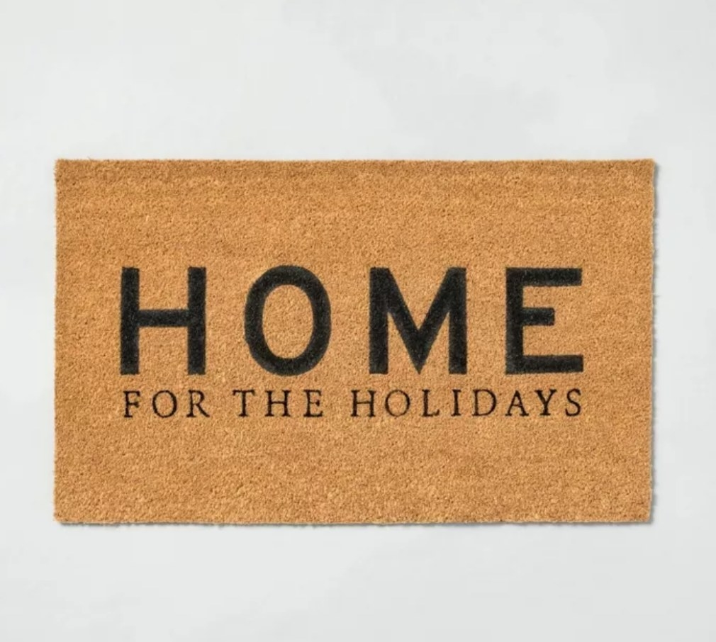 """""""Home for the Holidays"""" in black font on tan doormat"""