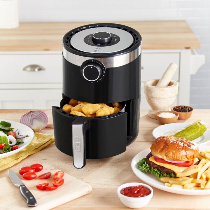 A kitchen counter that holds the air fryer and a bunch of food, like burgers, fries, chicken nuggets