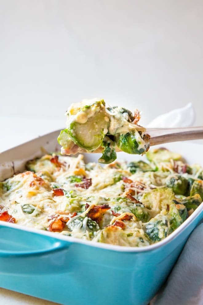 A wooden spatula taking a scoop of cheesy Brussels sprouts au gratin from a baking dish.