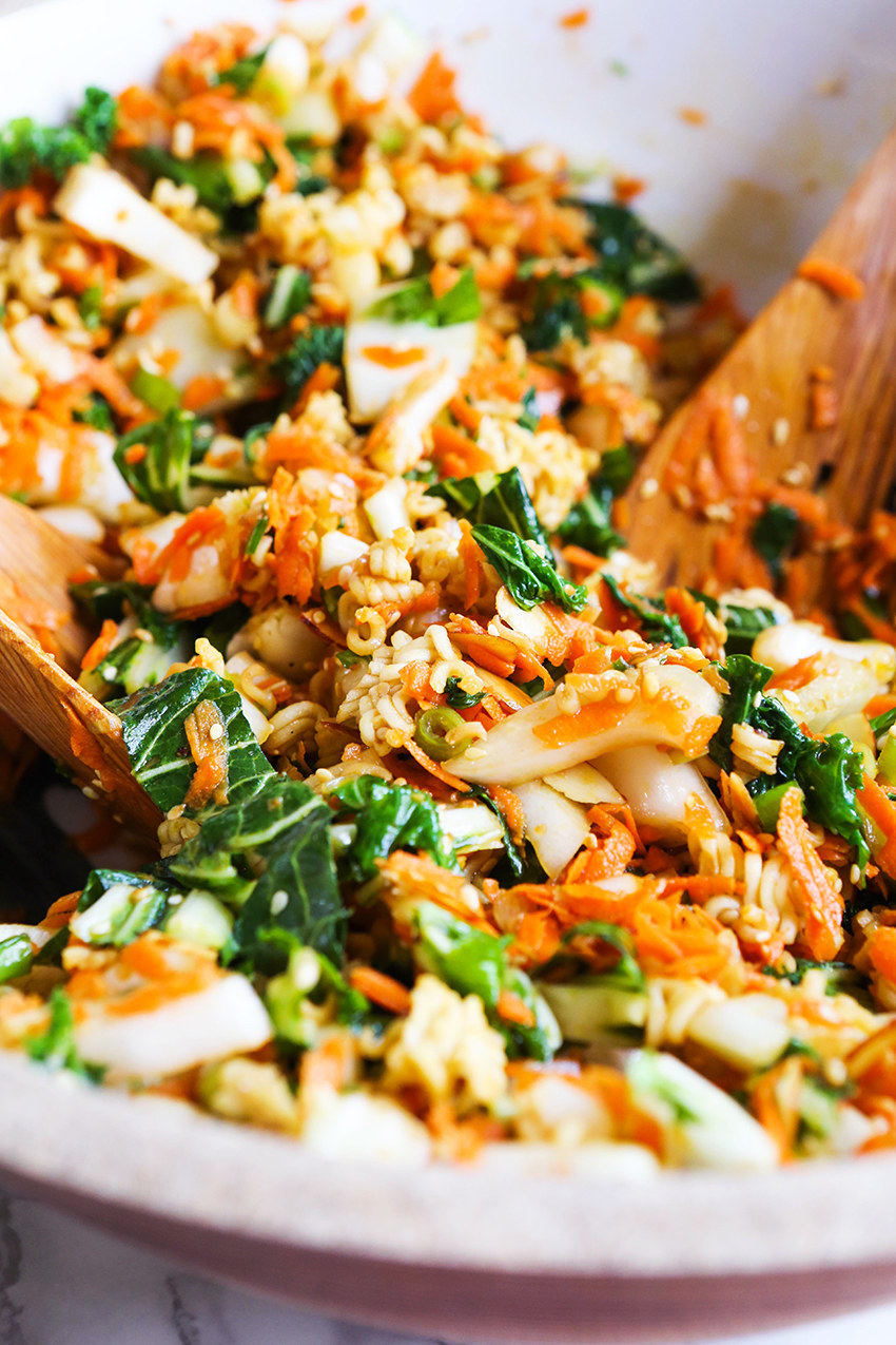 A big salad with bok choy, ramen noodles, carrots, almonds, and scallions.