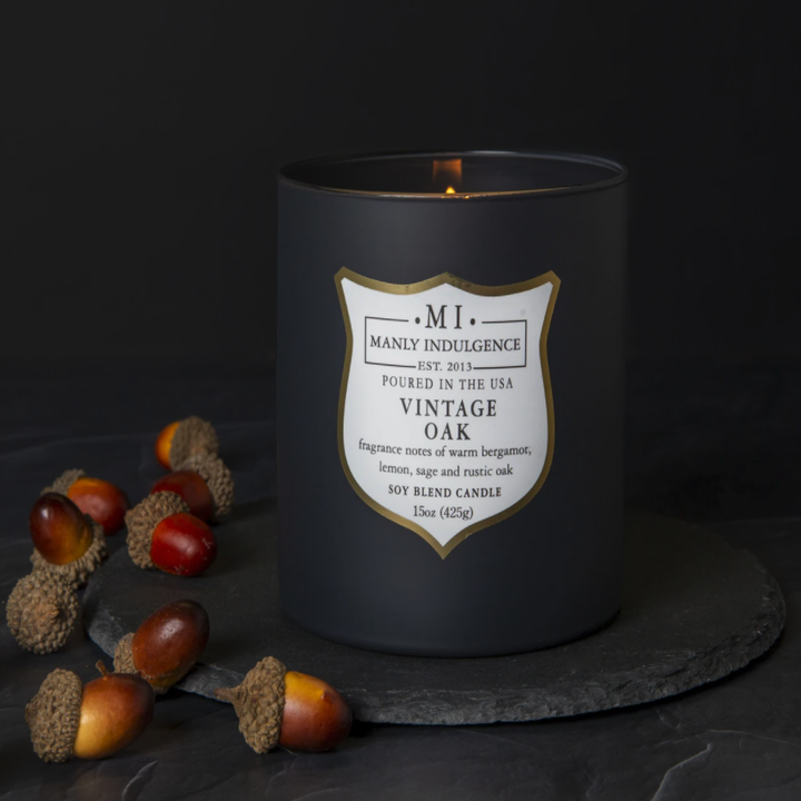 A close-up of a Vintage Oak-scented candle, with acorns next to it