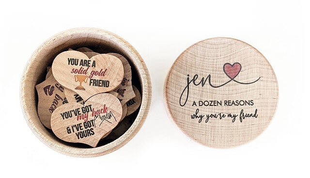 """A collection of 12 wooden hearts with different messages on them inside their box with a lid that reads """"Jen a dozen reasons why you're my friend"""""""