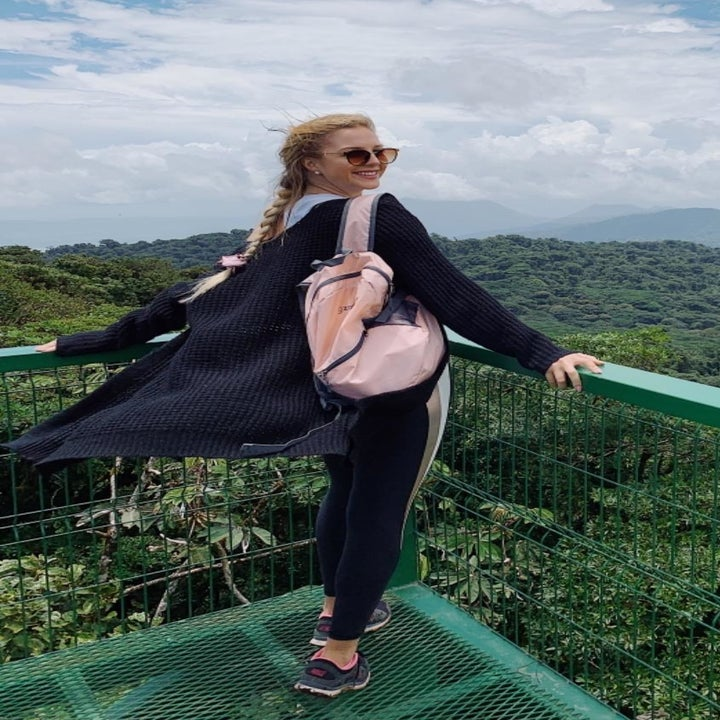 Reviewer wearing pink backpack looking out into a rainforest