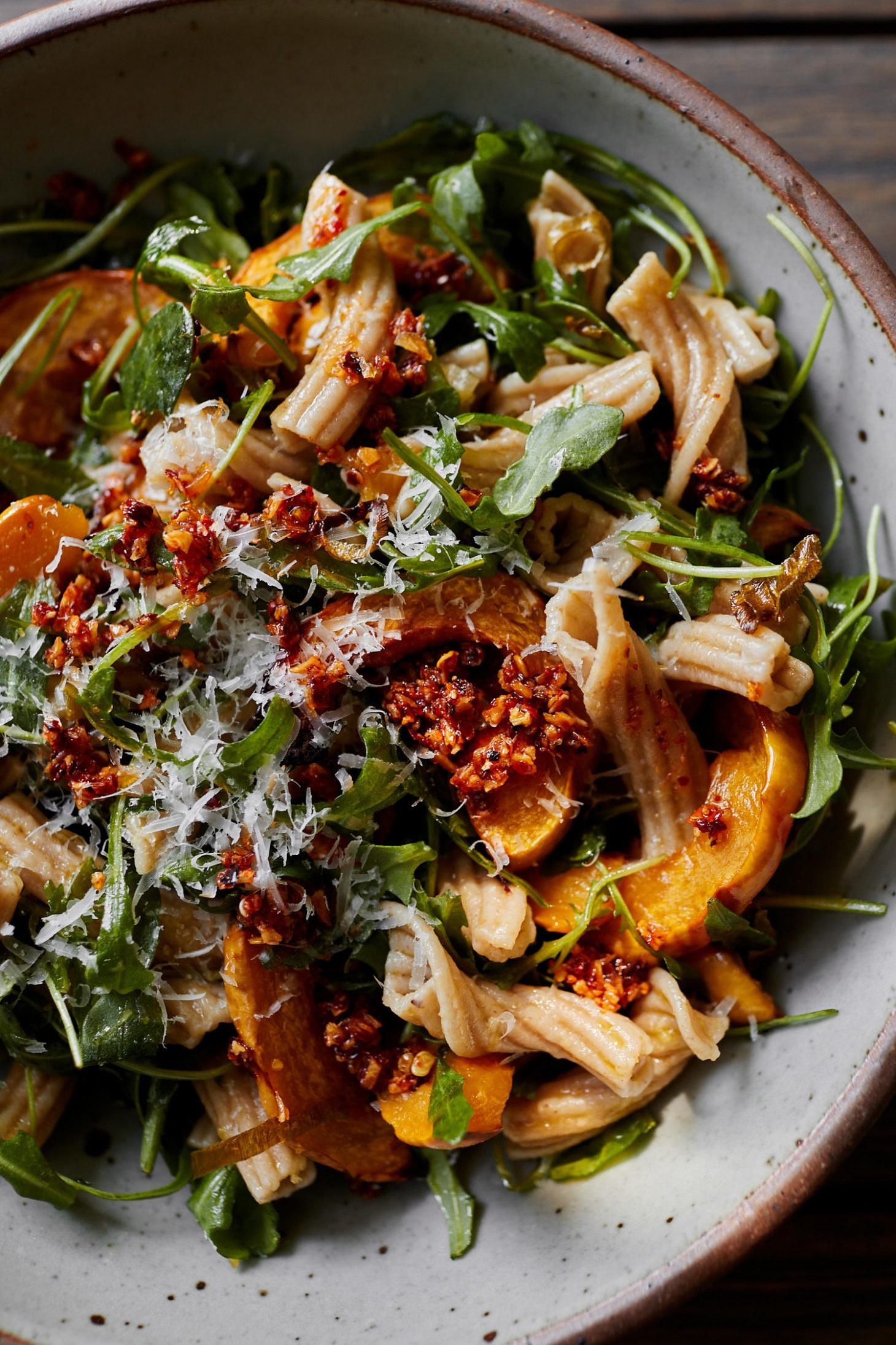 A bowl of pasta with arugula, delicata squash, and walnuts.