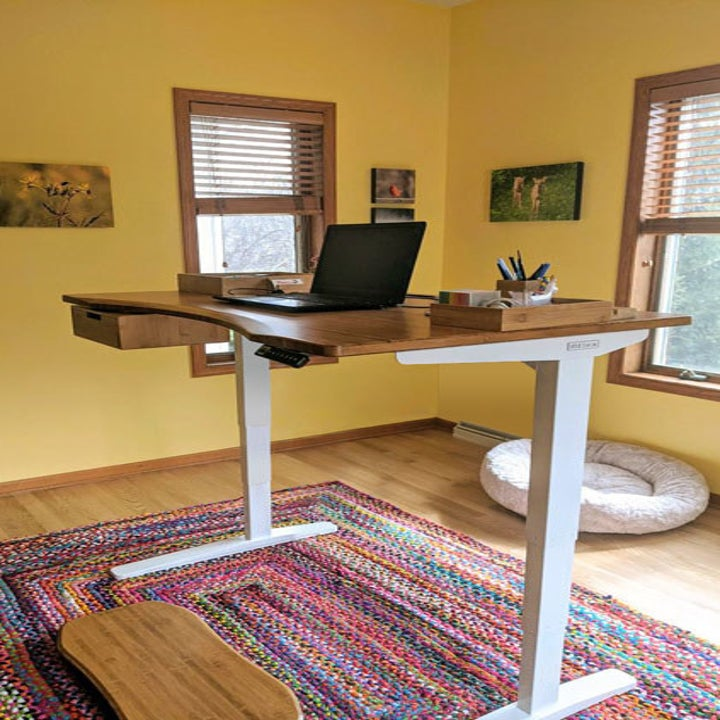 Customer photo of a standing desk with a brown wooden top, white base, a wooden drawer, multiple wooden trays, and a wooden motion board for standing on