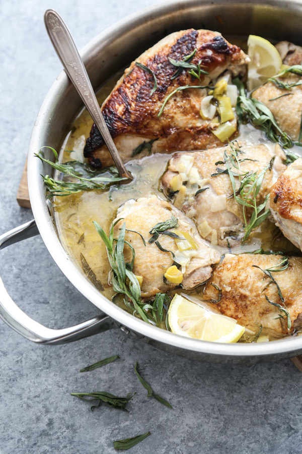 A skillet of braised chicken thighs in a creamy ginger leek sauce sprinkled with fresh herbs.