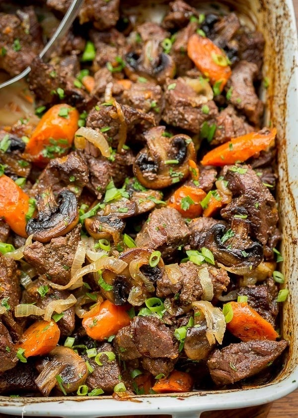 A casserole dish filled with roasted beef, carrots, mushrooms, scallions, and caramelized onions.