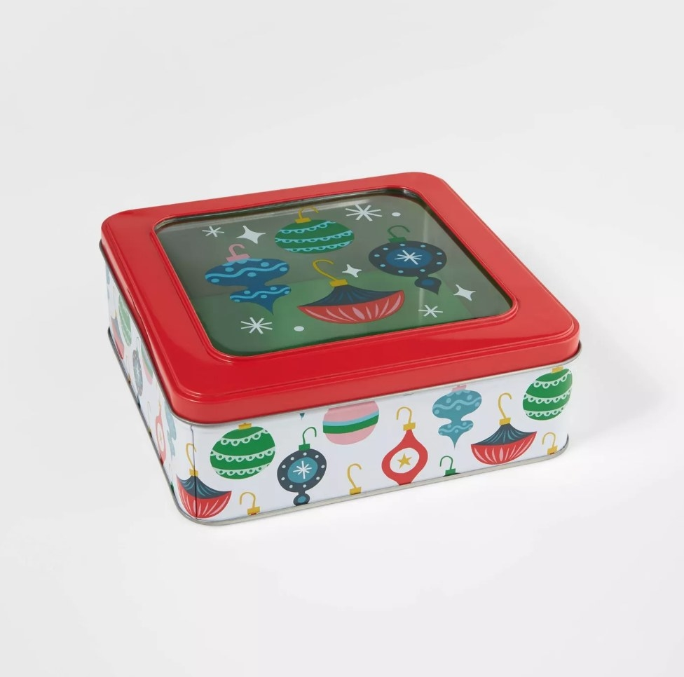Decorative cookie tin with white base with ornaments on it, red lid with ornaments