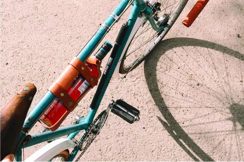 A top down shot of a blue bike with a bottle of wine hanging from the frame.