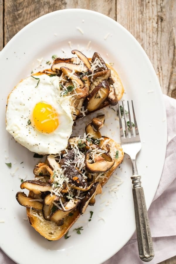 Two slices of toast topped with mushrooms, cheese, and a fried egg.