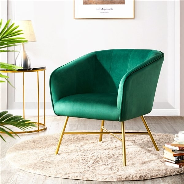a green chair with gold legs