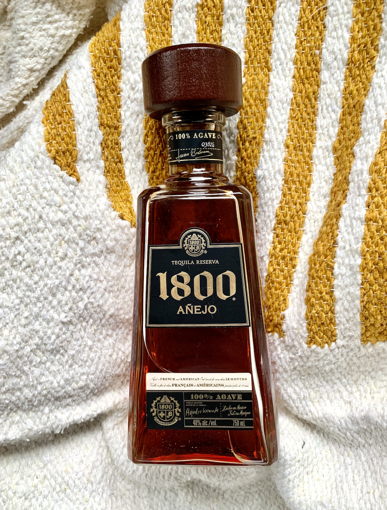 A bottle of 1800 Anejo against a a white and yellow fabric.